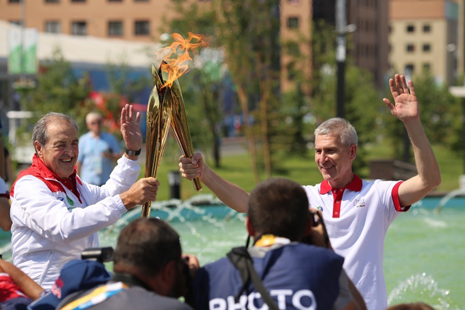 Oleg Matytsin (right) holding the Kazan 2013 Universiade flame with former FISU President Claude-Louis Gallien.